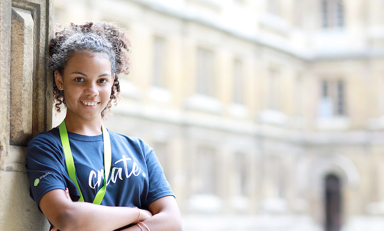 girl in navy shirt leaning against school building