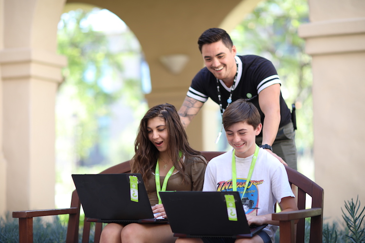 two students on bench with laptops