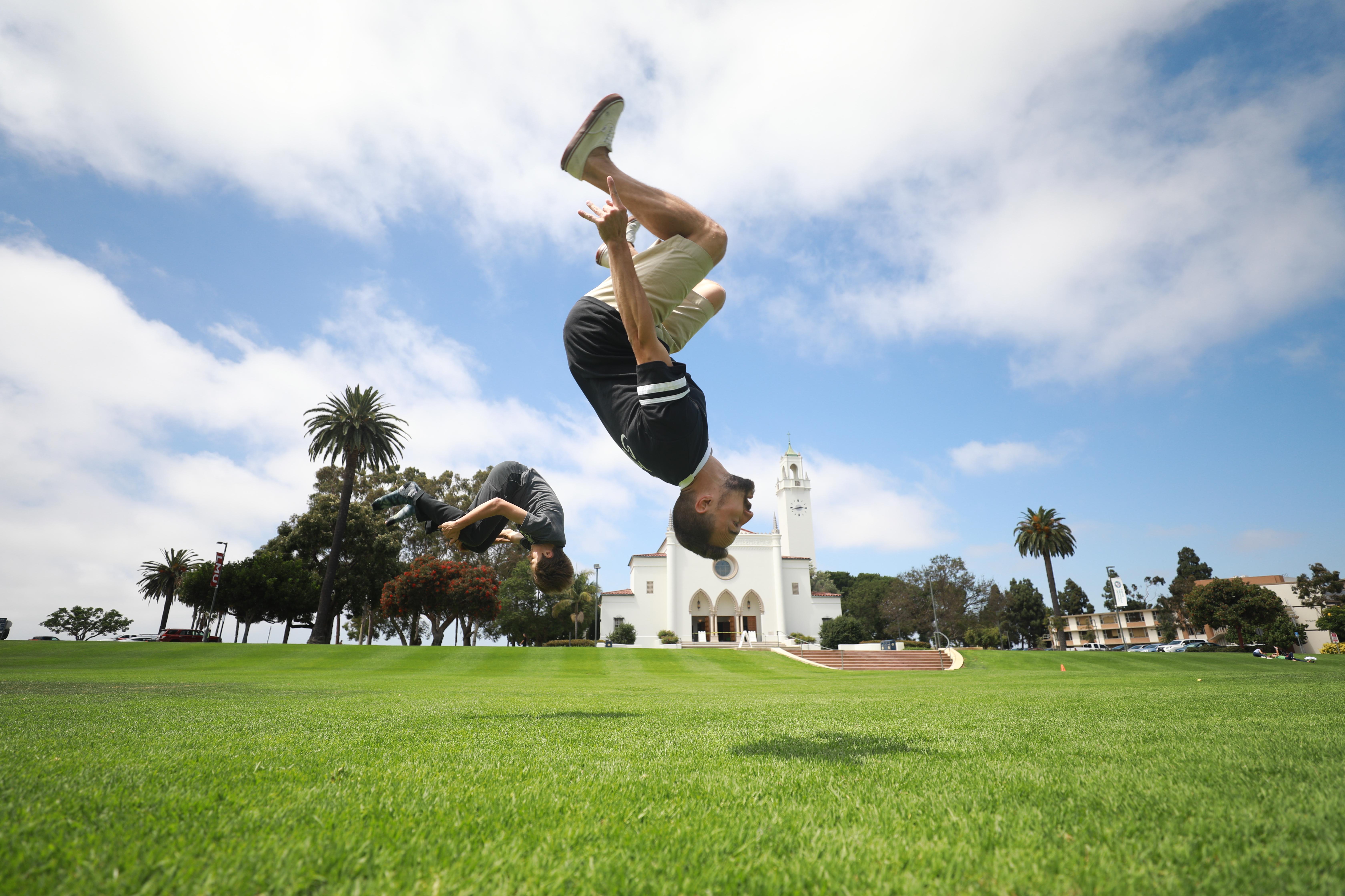 Kid doing a backflip on grass field