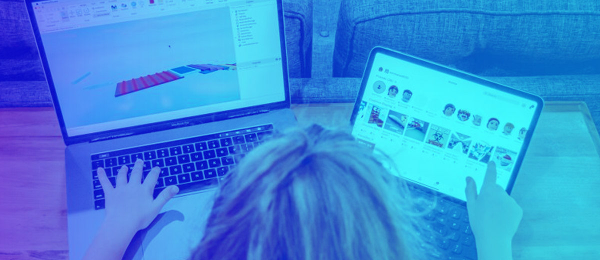 Overhead view of girl at desk with two laptops