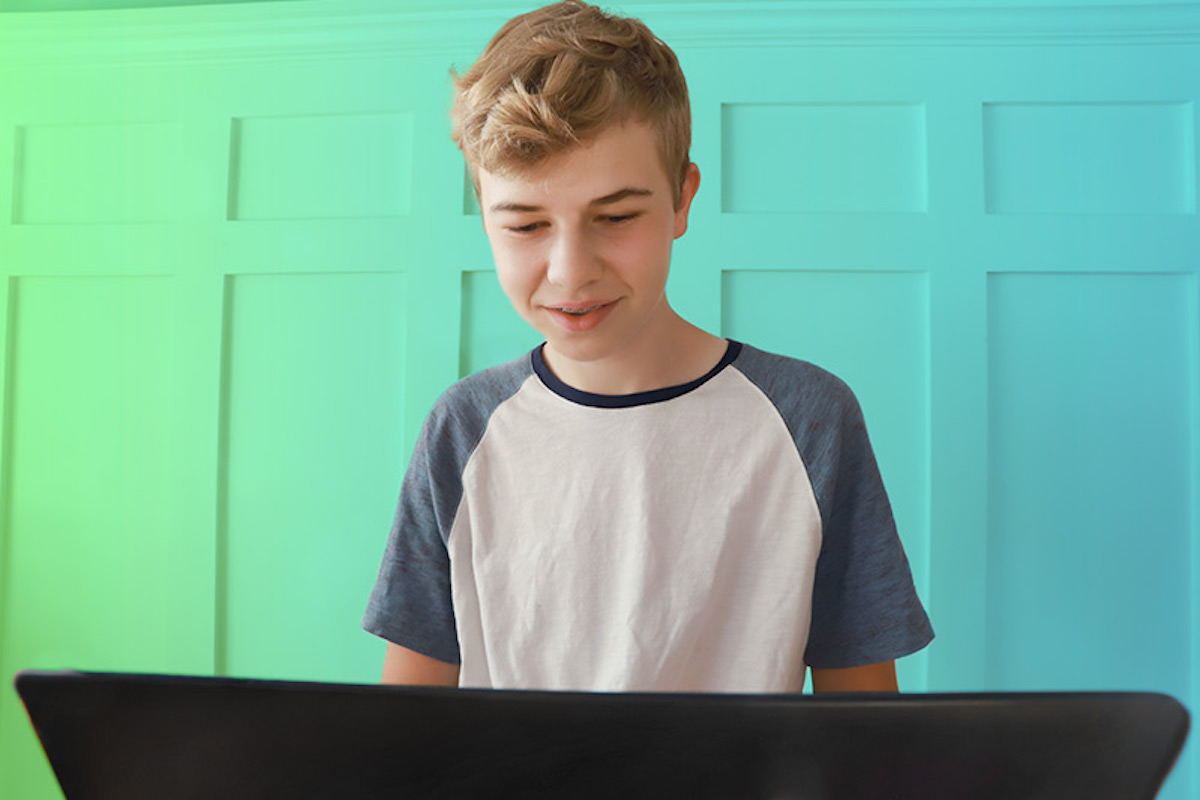 boy looking down at laptop green background