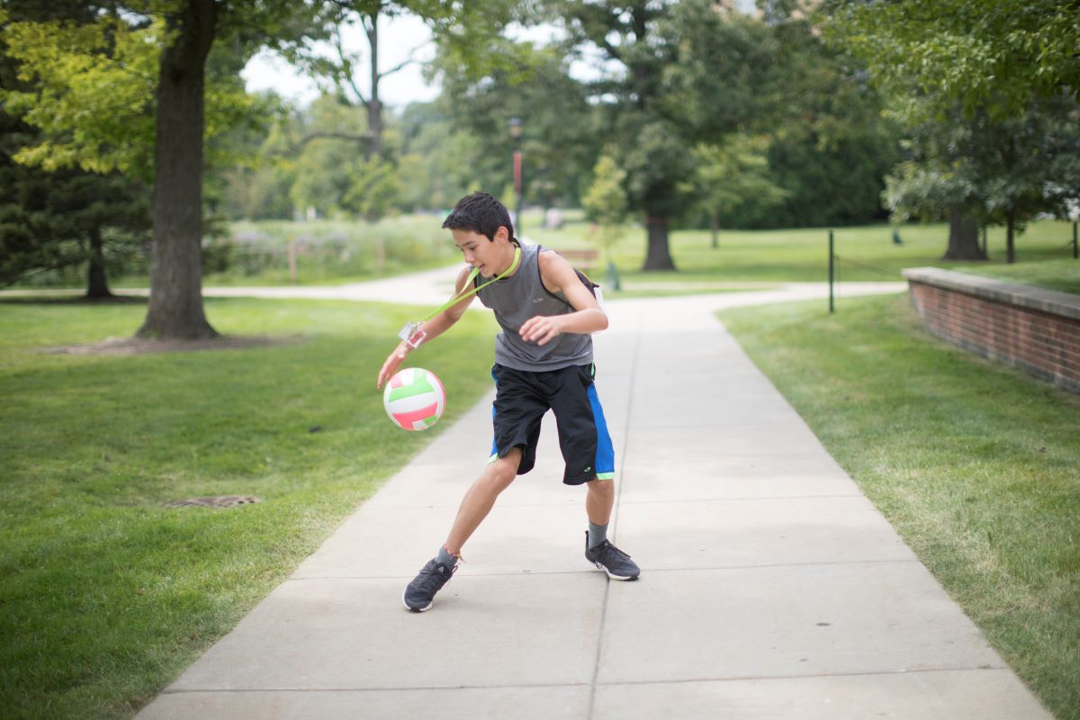 boy dribbling basketball down park sidewalk