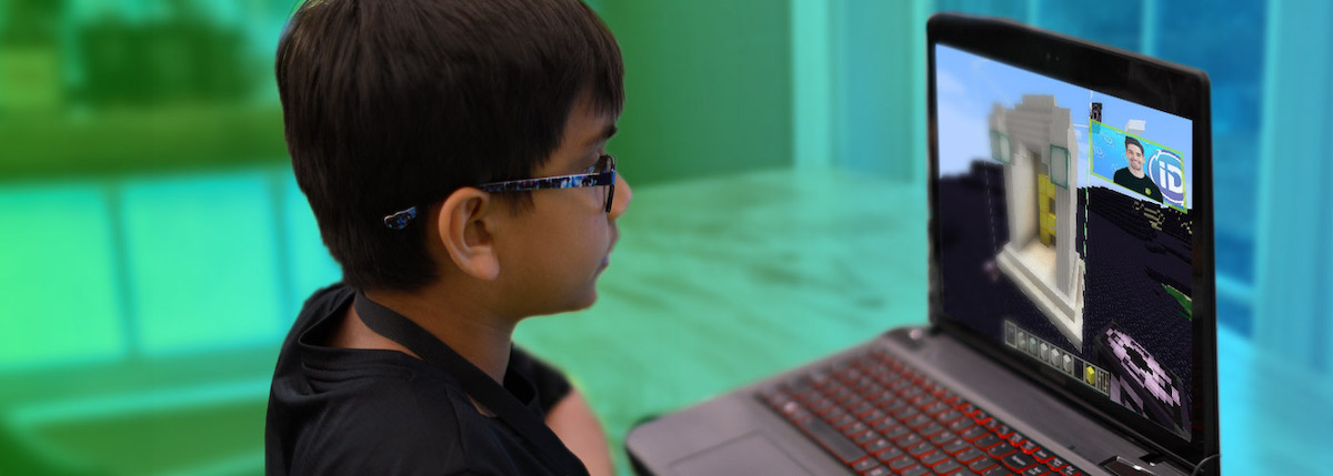 boy with glasses playing minecraft on laptop