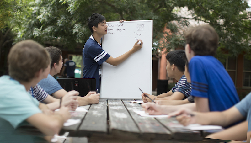 students taking notes while instructor writes on whiteboard