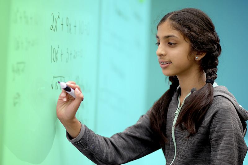 girl at whiteboard writing math equation