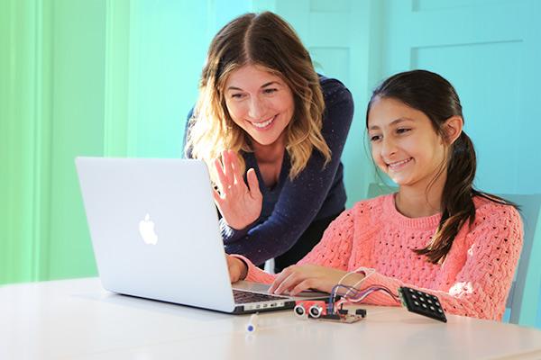 mom over daughter's shoulder waving at laptop computer