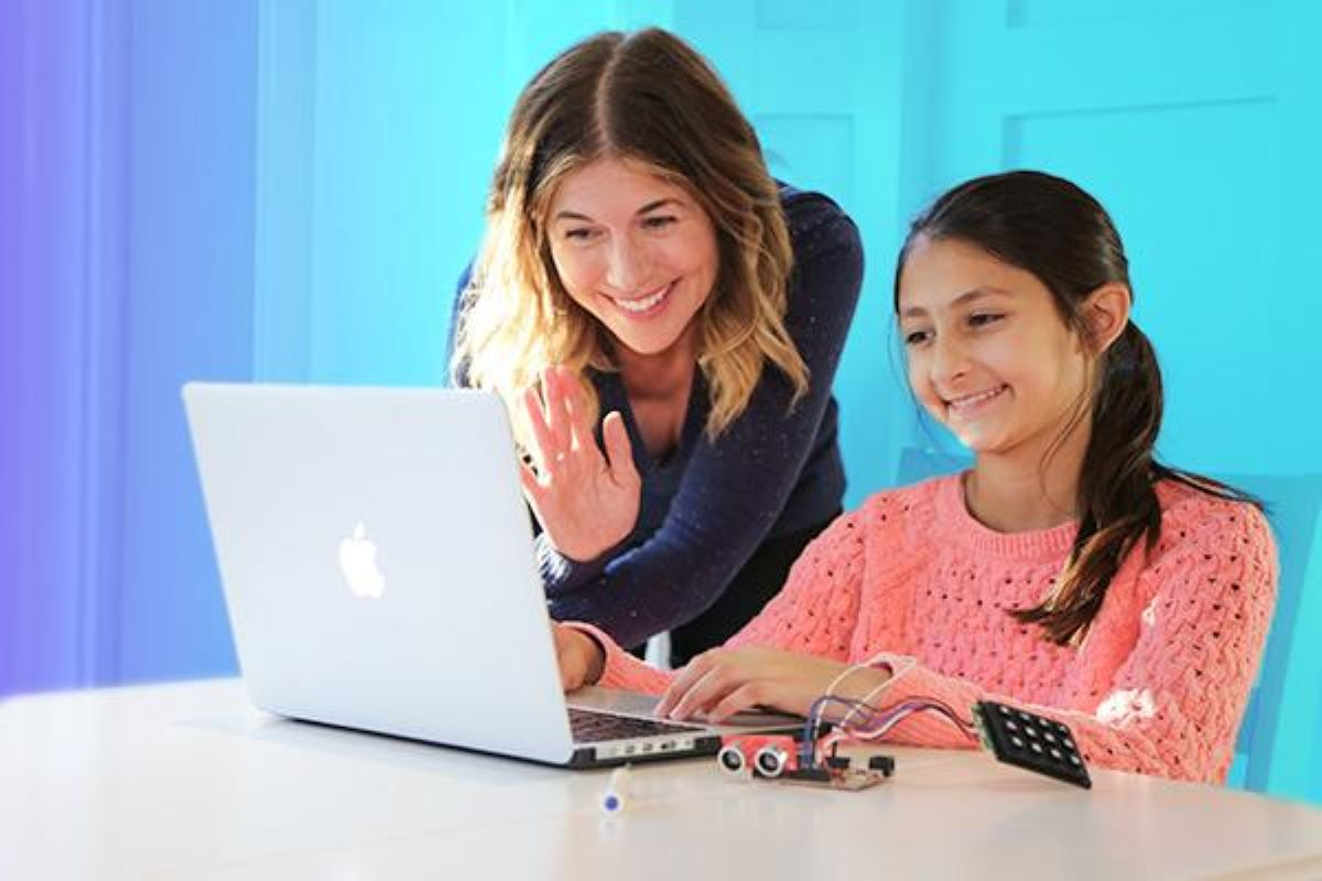 Mom looking over daughter's shoulder and waving at teacher on computer
