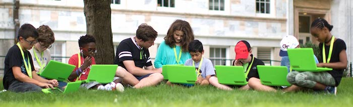 Summer campers outside on computers