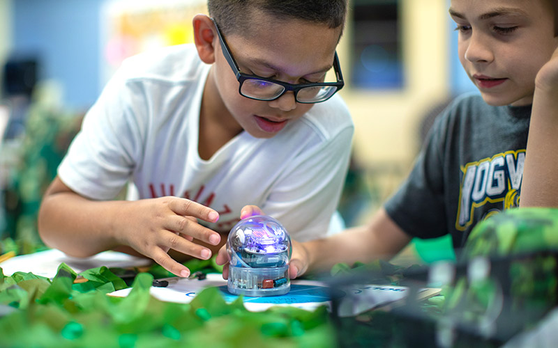 two boys in classroom with sphero robot