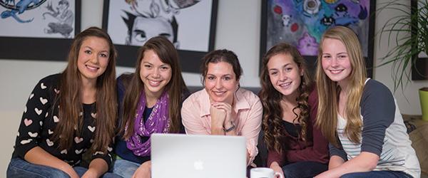 girls gathered around laptop