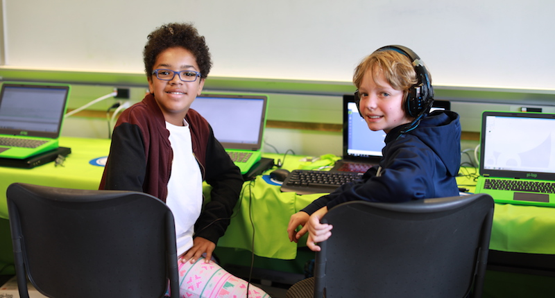 two students sitting at laptops