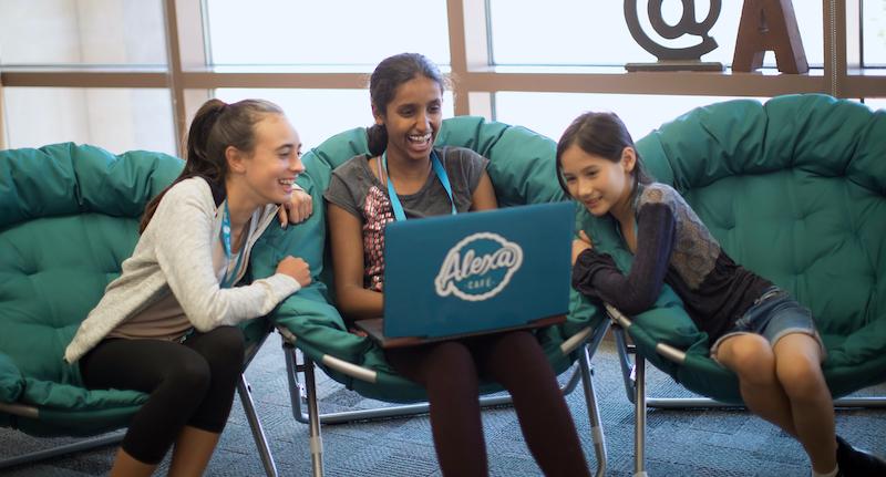three girls sitting in chairs around blue laptop