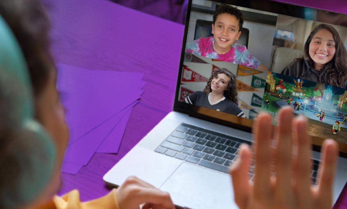 boy waving to zoom friends on laptop